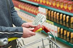 Bank card and dollar bills in hand at store royalty free stock image