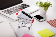 Bank card nearby a laptop and mini shopping cart. Woman forefinger pushing small shopping cart with Internet online shopping concept. Bank card nearby a laptop stock images
