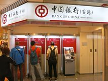 Bank of China. A line of ATMs for the Bank of China (Hong Kong) with people waiting to get out money or deposit it in their account Royalty Free Stock Photography