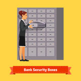 Bank clerk woman opening safe-deposit box Stock Photos