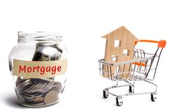 Bank with coins and the inscription Mortgage and a house in a trolley supermarket. Buying a house or apartment loans. Payment of. Mortgage rates and tax. Debt stock photo