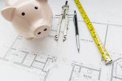 Bank, Compass, Pencil and Measuring Tape Resting on House Plans Stock Photography
