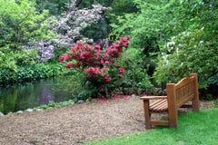 Bank in de tuin stock afbeeldingen