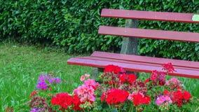 Bank des rosa Gartens im Freien mit Blumen und Zubehör Stockbilder