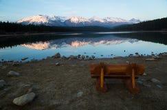 Bank durch See mit Bergen im Horizont Stockbilder