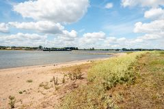 Bank of the Dutch river De Waal in the summer season. Sandy beach on the banks of the Dutch river Waal in the summer season. The water level is low because of royalty free stock image