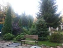 Bank in een groene tuin Stock Afbeelding