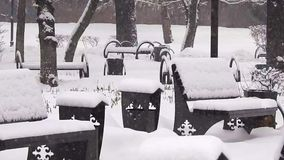 Bank in een park van de sneeuwvalstad stock video