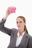 Bank employee holding piggy bank over her head. Against a white background Royalty Free Stock Image