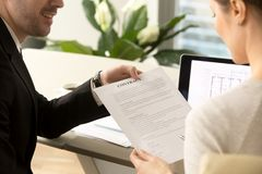 Bank employee offering loan contract to woman. Male credit expert or real estate agent offering female client sign contract to buy apartments or house. Woman Royalty Free Stock Photography