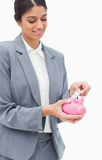 Bank employee putting bank note into piggy bank Stock Photos