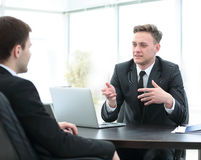 Bank employee sitting behind a Desk and talks to the client Stock Images
