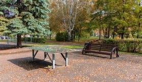 Bank en een tennislijst met gevallen geel gebladerte van de bomen, in de herfst in het park een warme dag Stock Afbeeldingen