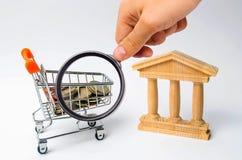 Bank en het karretje met geld Het concept dividendbetalingen, stortingen in banken Bankwezensysteem, investering in de economie royalty-vrije stock foto