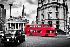 Bank of England, the Royal Exchange in London, the UK. Black taxi cab and red bus. Bank of England, the Royal Exchange in London, the UK. Iconic black taxi cab royalty free stock image