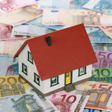 Bank financing a real estate with a house on banknotes Royalty Free Stock Photography