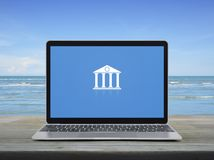 Business banking online concept. Bank flat icon with modern laptop computer on wooden table over tropical sea and blue sky with white clouds, Business banking stock photo