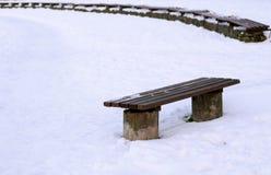 Bank im Park bedeckt mit Schnee am sonnigen Tag des Winters Feld des grünen Grases gegen einen blauen Himmel mit wispy weißen Wol stockbilder