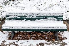 Bank im Park mit Schnee Stockbilder