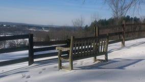Bank im Schnee durch Zaun Stockbild