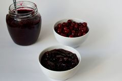 Bank with jam and cranberries on white background royalty free stock image