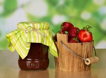 Bank with jam and strawberyy in wooden bucket. Bank with jam and a bucket with strawberry, on a table Stock Photography