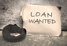 Bank loan. Loan wanted sign written on a piece of cardboard with a begging hat stock image