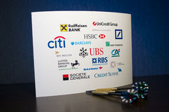 Bank Logos on the White Paper and three Darts Royalty Free Stock Photography
