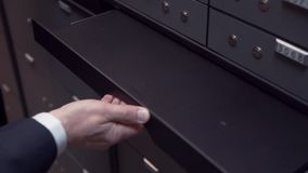 Bank manager hands pulls out foldable table in safe depository for client to use stock footage