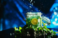 Bank mojito with lime and mint ice cube falling splash Royalty Free Stock Photos
