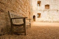 Bank nahe einer mittelalterlichen Wand Stockfoto