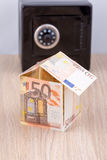 Bank note house with metal coin bank Stock Image