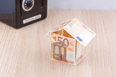 Bank note house with metal coin bank Royalty Free Stock Photos