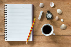 Bank notebook with pencil and eraser laying on the brown table. Vintage clock at 8 o'clock, Black coffee and shells on table royalty free stock photography