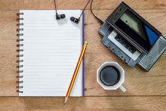 Bank notebook with pencil laying on the brown table. Vintage old tape player with earphones and black coffee put on the table as well stock photography
