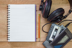 Bank notebook with pencil laying on the brown table. Vintage old tape player with headphones put on the table as well royalty free stock images