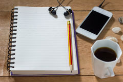 Bank notebook with pencil laying on the brown table. White mobile with earphones and black coffee put on the table as well stock image