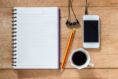 Bank notebook with pencil laying on the brown table. White mobile with earphones and black coffee put on the table as well stock photos