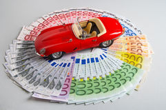 Bank notes. Model of a car lying on the circle of money Royalty Free Stock Photography