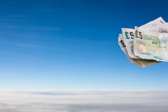 Bank notes floating in a blue sky. Above clouds Royalty Free Stock Photography