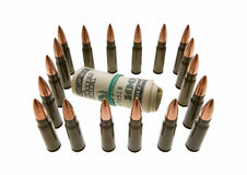 Bank notes roll and bullets - secured cash concept Stock Photos