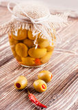 Bank of olives with pepper. On a wooden board Stock Image