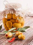 Bank of olives with pepper on a wooden. Board Stock Images