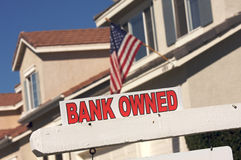 Bank Owned Real Estate Sign and House with America. N Flag in the Background stock photography