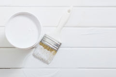 Bank paints and brush on white wooden background Stock Photo