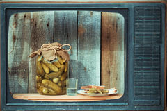 Bank of pickles, vodka and snack in the old TV. Image in the soft blue toning Royalty Free Stock Photo