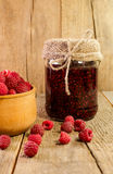 Bank of raspberry jam and fresh raspberries. On a wooden surface Royalty Free Stock Photos