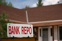 Bank Repo Sign on Home For Sale. Close up and focus on a Bank Repo sign with a house in the background stock photo
