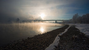 Bank of the river and the bridge in the fog Stock Photo