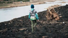 The bank of the river with burnt grass. The boy walks through the ashes